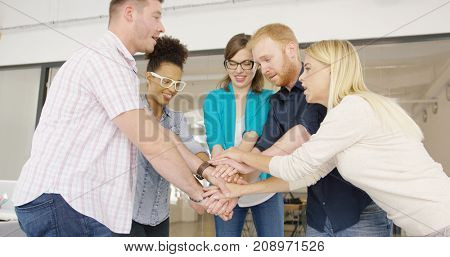 Side view of group of young promising coworkers standing in circle and stacking all together showing high spirit of team unity.