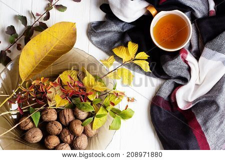 autumn picture with yellow red and orange leaves a cup of tea a scarf. Cup of tea and autumn leaves on a white wooden table
