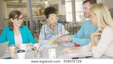 Casual man sitting with female coworkers at table and showing them folder with documents while discussing important issue.