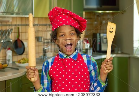 Black kid with cooking utensils. Boy in the kitchen. Basic cooking skills.