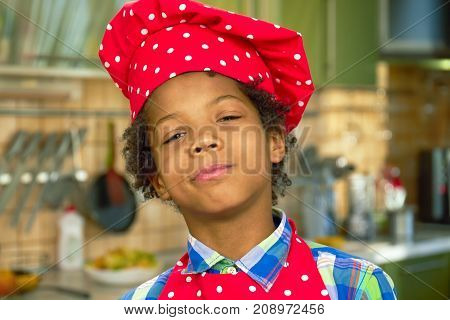 Black boy in chef hat. Cute proud kid.
