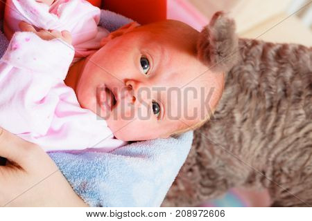Little newborn baby in pyjamas lying on back with cat tail in background. Surprised face expression. Family parenthood childhood concept.