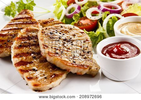 Grilled steaks and vegetable salad on white background