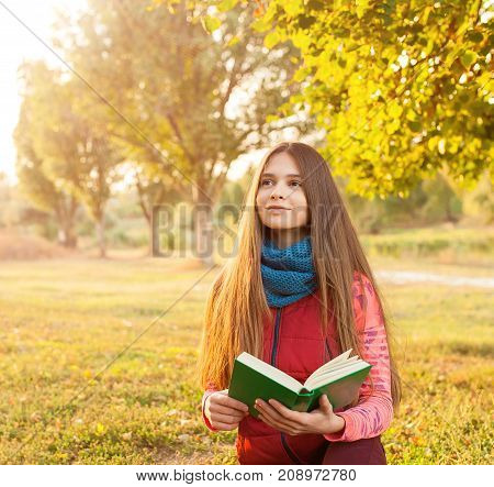 Portrait of a young girl reading a book on a background of autumn colour park. People concept