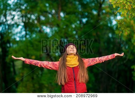Brunette woman happy smiling joyful with arms up dancing in autumn holidays.Young woman outdoors. Freedom concept.