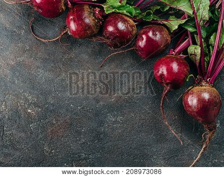 Beet, beetroot bunch on dark stone or concrete background. Fresh ripe beetroot with leaf on dark table. Copy space. Top view or flat lay
