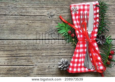 Christmas table place setting with christmas pine branchesribbon and cones. Christmas holidays background. top view with copy space
