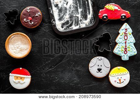 Make gingerbread cookies for new year 2018. Sweets near baking sheet on black background top view.