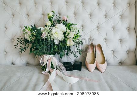 White wedding bouquet, pink bridal shoes and black boxes with rings on a luxury sofa. Indoors. Artwork