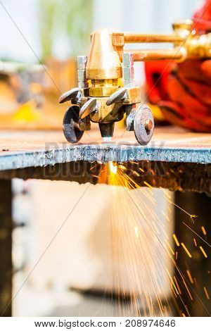 Sparks fly in closeup cutting plate steel with arc welder.