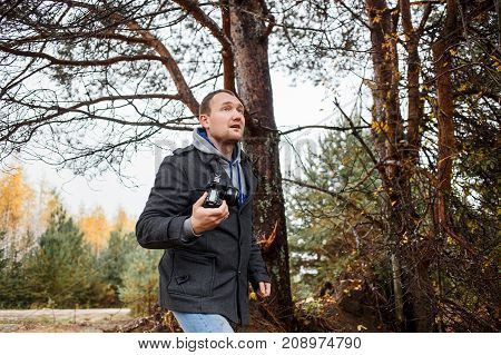young hiker photographer photographing in autumn forest.