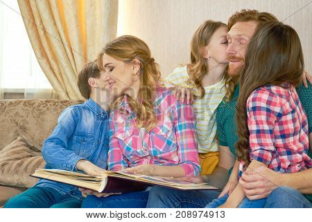 Family with photo album indoors. Children kiss parents. We love you dad.