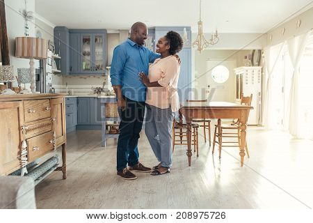 Affectionate African couple smiling at each other while standing arm in arm together in their kitchen at home