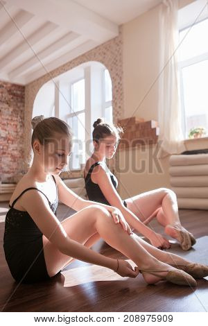 Young ballerinas. Pensive ladies in class. Teenage sport, pretty girls stretching. Sensibility from childhood. Gym background, healthy teen lifestyle, femininity concept