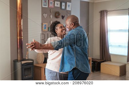 Affectionate mature African couple enjoying a playful moment while dancing together in their living room at home