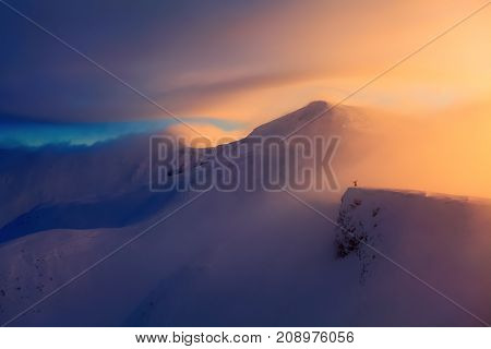 Fantastic scenery with a free rider and mountaineer high mountains in snow and the fog with interesting colour from the sun in the winter day.