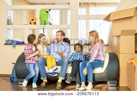 Family sitting on sofa relocation. Parents with children, cardboard boxes.
