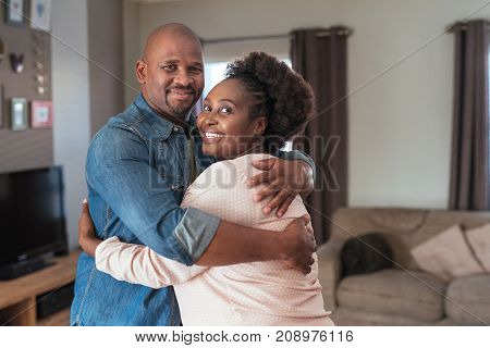Portrait of a content African couple smiling and hugging each other while standing together in their living room at home