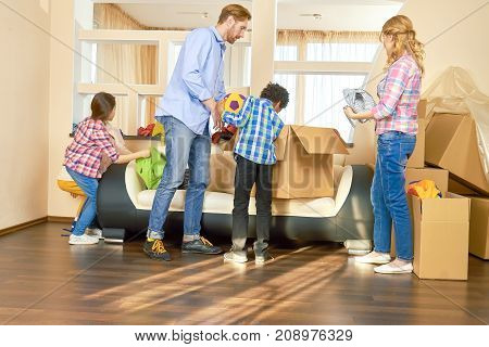 Family indoors relocation. Parents with kids cardboard boxes.