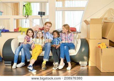 Family taking selfie indoors. Joyful people near cardboard boxes.