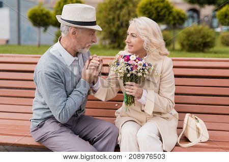 Two pensioners are sitting on a bench in the alley. The aged man gave the woman flowers. She is delighted with the gift. He gently kisses her hand