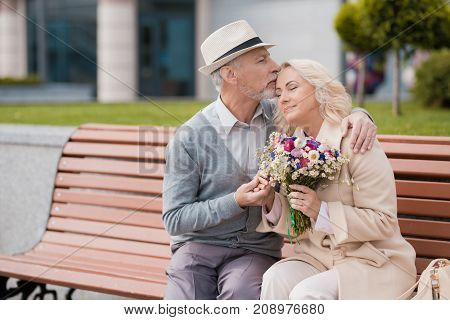 Two pensioners are sitting on a bench in the alley. The aged man gave the woman flowers. She is delighted with the gift. He kisses her forehead tenderly
