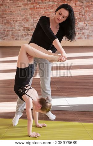 Young ballerina life. Help in teaching. Sport for girls, rhythmic gymnastics in dance class with female instructor. Gym background, healthy teenager lifestyle, femininity concept