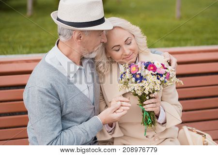 Two pensioners are sitting on a bench in the alley. The aged man gave the woman flowers. She is delighted with the gift. He gently holds her hand