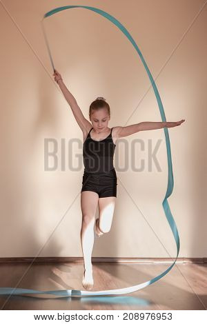 Rhythmic gymnastics. Graceful girl in motion. Teenage sport, healthy teen lifestyle. Attentive ballerina with blue ribbon, brown background with free space, exercise concept