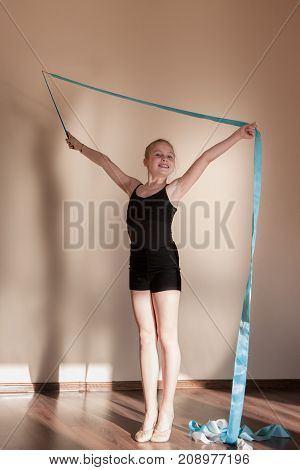 Rhythmic gymnastics. Happy confident ballerina. Teenage sport, healthy teen lifestyle. Smiling young girl with blue ribbon, brown background with free space, ballet concept
