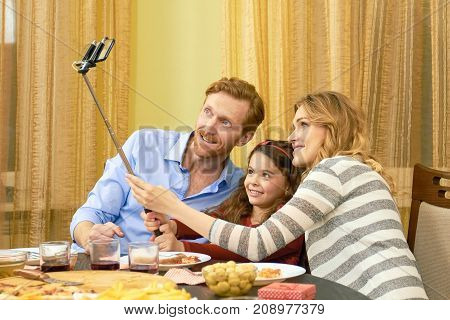 Family taking selfie during dinner. Parents and daughter smiling. Our happy moments.