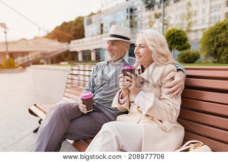 Two pensioners are sitting on a bench with a glass of coffee in their hands. They sit embracing and smiling. Pensioners are looking into the distance