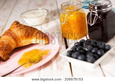 Breakfast with croissant blueberries yogurt orange and blueberry jam over a wooden table