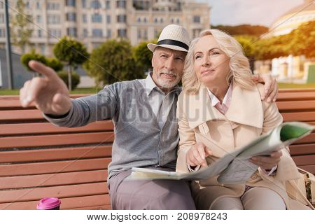 Two pensioners sit on the bench and study the map of the city. They watch the map with interest and wonder where they will go next.