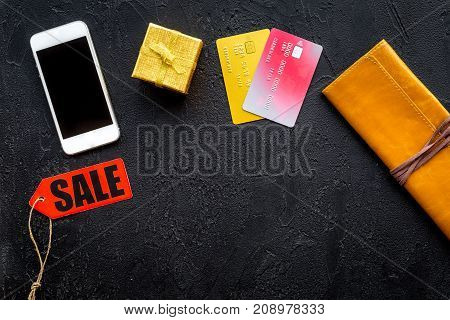 online payment for christmas present with credit card and mobile on dark black table background top view mockup