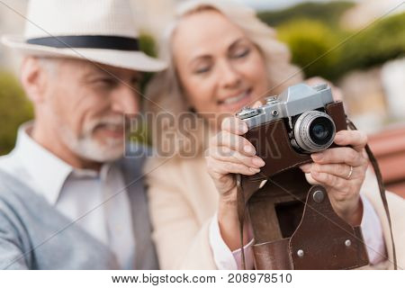 Two pensioners are sitting on the bench and studying a vintage camera. They are going to take some photos on the old camera