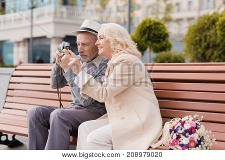 Two pensioners sit on a bench and take photos on an old film camera. They smile and are very happy. Against the backdrop of a beautiful urban development