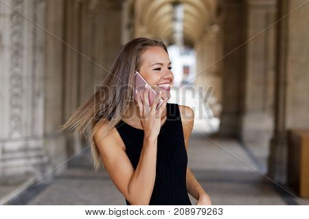 Happy young brunette woman calling by smartphone outdoor