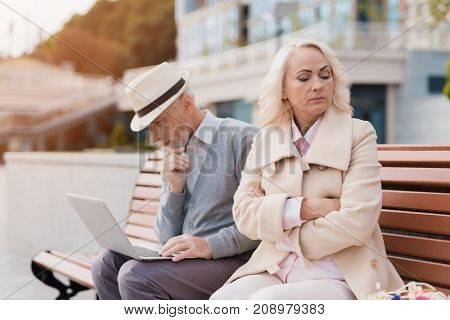 A couple of retired people are sitting on a bench in the mall. A man is working on a laptop, a woman is offended at him and turned away. She frowns.