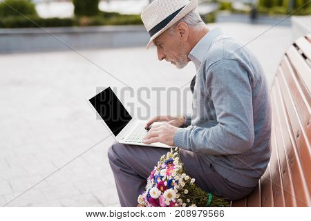 The pensioner sits on the bench and works behind the laptop. He sits on a bench in the alley. Next to him lies a bouquet of tsuets, he is waiting for a woman