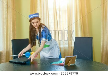 Young maid working. Housemaid cleaning office. Employment outlook in hospitality industry.