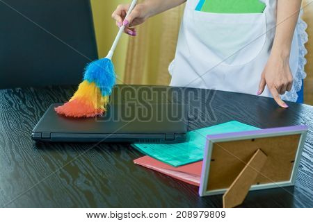 Hands of housemaid, dusting. Woman using a dust brush.