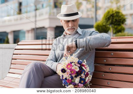 A pensioner is sitting on a bench waiting for a woman. They should have a date. He has a bright hat and he has flowers in his hands