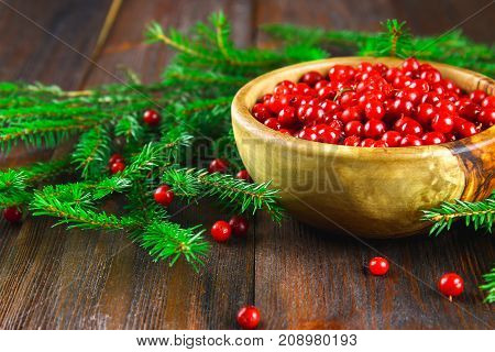 Cowberry, Foxberry, Cranberry, Lingonberry In A Wooden Bowl On A Brown Wooden Table. Surrounded By F
