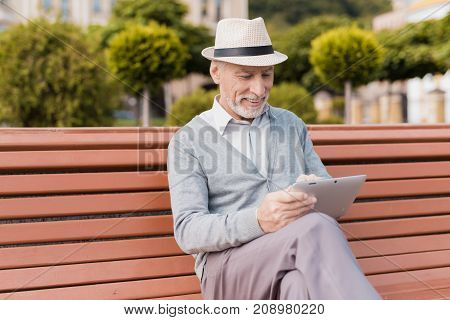A pensioner sits on a bench in a beautiful square. He has a gray tablet in his hand. He is reading something on his gray tablet