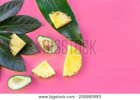 Tropical fruits background. Pinneapple and avocado slices, big leaves on pink background top view.