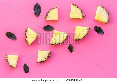 Exotic fruits pattern. Pinneapple slices on pink background top view.