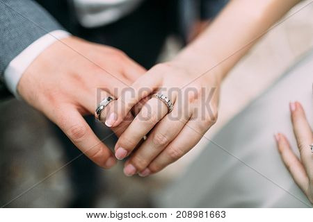 Just married young couple showing up their rings. Wedding outdoors. Artwork. Soft focus