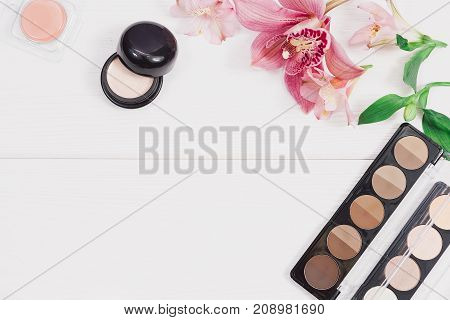 Decorative flat lay composition with makeup products, cosmetics and flowers. Flat lay, top view on wooden background. Copytext