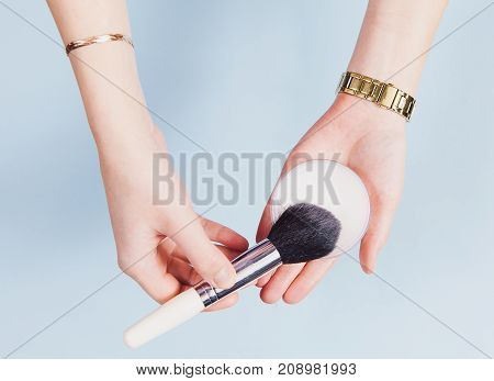 Flat lay with hands holding visage brush and powder. Accessories and decorations on the blue background. Indoor